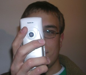 Young man taking a picture with a smart phone camera