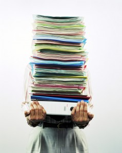 person holding a huge stack of reports